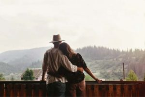 cute-couple-leaning-on-each-other-overlooking-mountains