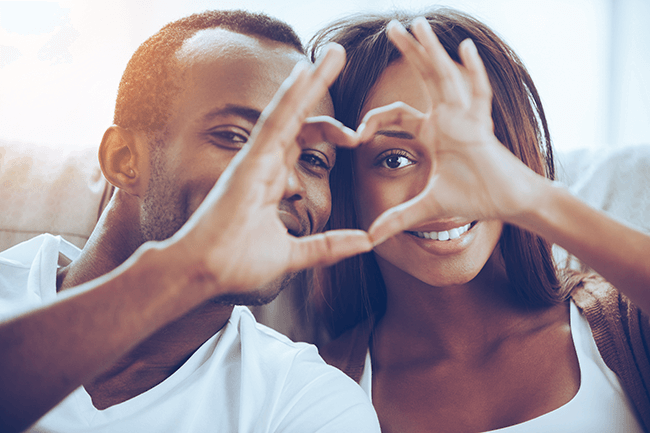 african-couple-making-heart-with-hands-and-smiling