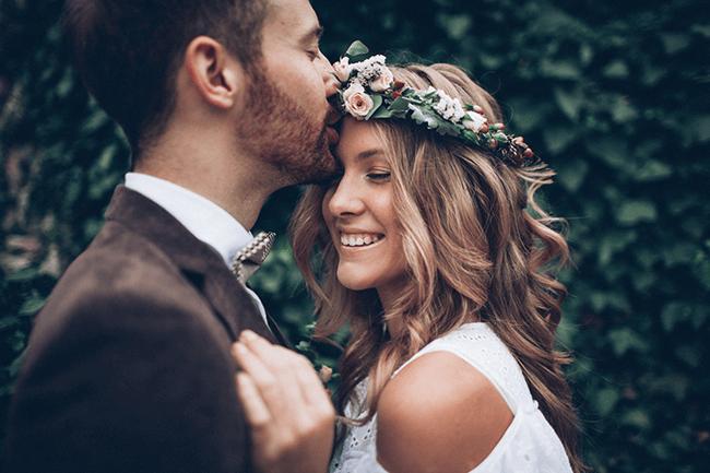 bride-smiling-as-husband-kisses-her