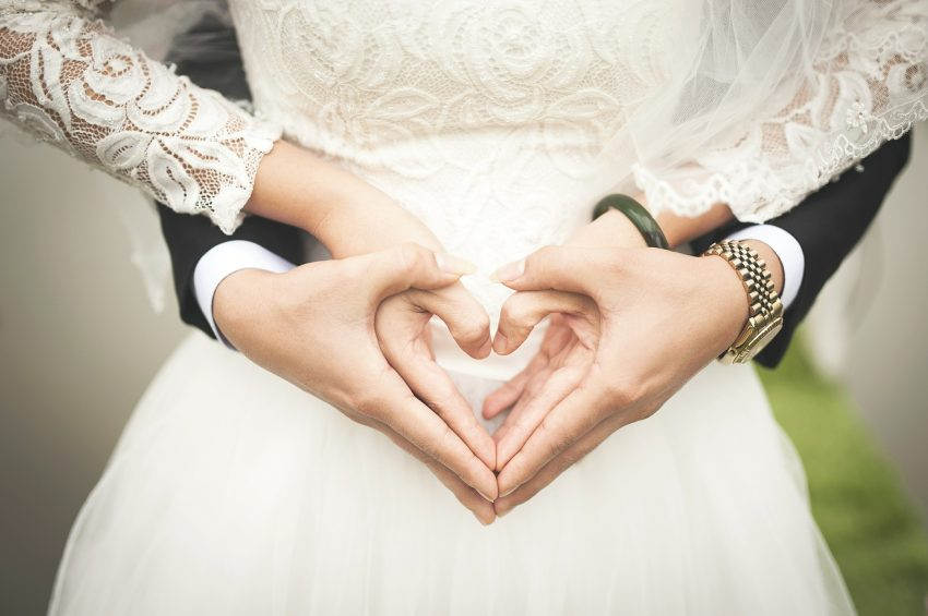 bride-holding-groom-making-heart-with-hands