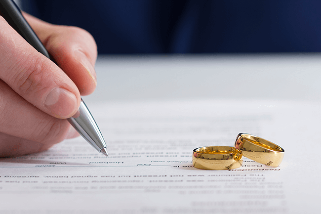 husband-signing-divorce-decree-with-wedding-rings-in-front