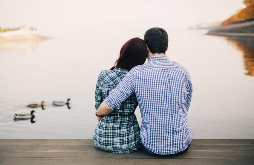 couple-sitting-on-dock-feeding-ducks