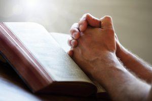 hands-lying-on-bible-praying