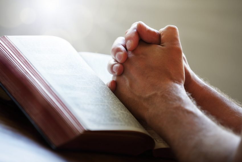 hands-lying-on-bible-praying