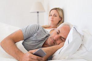 husband-suspiciously-looking-at-his-phone