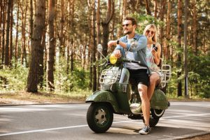 blonde-haired-woman-and-brown-haired-male-riding-a-motorcycle-in-the-forest